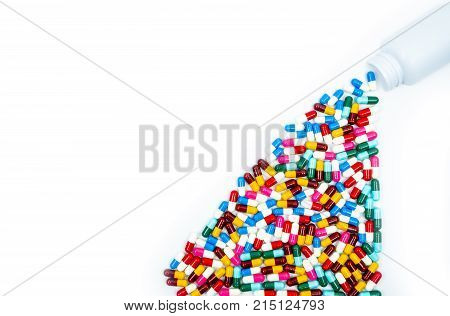 Antibiotic capsules spilling out of pill bottle on white background with copy space just add your own text. Drug resistance concept. Antibiotics drug use with reasonable and global healthcare concept
