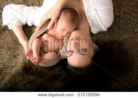 Beautiful Mother Embracing With Tenderness And Care Her Newborn Son, Shot From Above