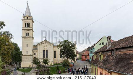 Sighisoara Romania October 08 2017 : Tourists walk around the square near Roman Catholic Church - Citadel in the castle of old city. Sighisoara city in Romania