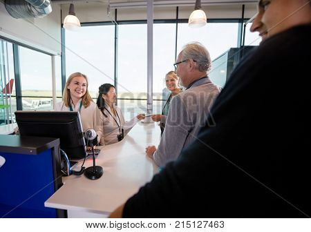 Smiling Staff Looking At Passengers At Counter In Airport