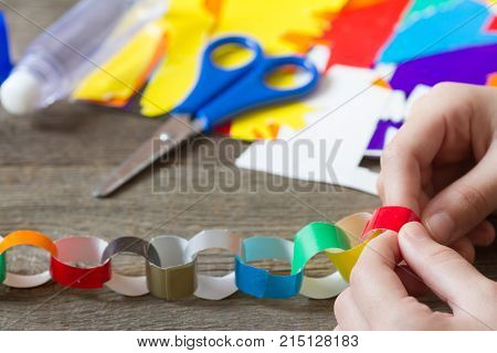 Making christmas paper chains by kid closeup