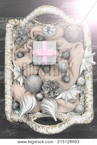 Decorative Christmas composition Christmas toys in the basket. Painted wooden background top view. Vertical format