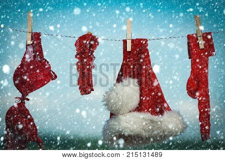 christmas new year snow Christmas clothes outdoor. New year costume on blue sky. santa clothes for drying. Laundry and dry cleaning. Xmas red costume on rope with pin.