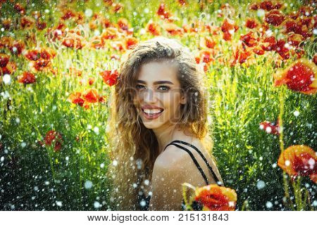 christmas new year snow girl with long curly hair hold flower in field of red poppy seed with green stem on natural background summer spring drug and love intoxication opium