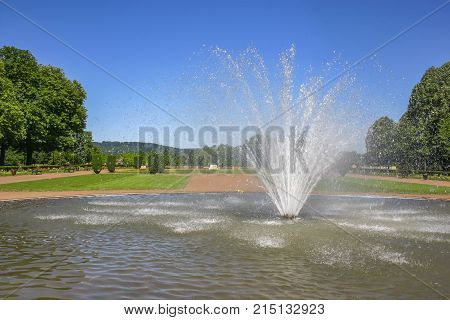 Public fountain with water jet flowing from the ground in a big green park in Metz located at the North Est of France at the Germany border