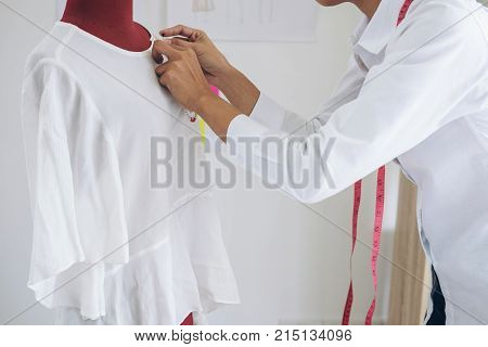 Young woman dressmaker or designer working as fashion designers measure and Repairing clothes and sewing for clothes as red dummy profession and job occupation Designer Stylish Concept.