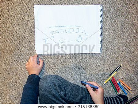 Little boy painting a bus on a paper with crayons at the kindergarden floor view from above