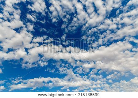 Moving white fluffy clouds at the blue sky