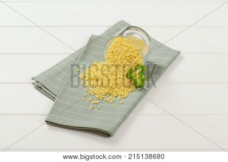 glass of uncooked alphabet pasta spilt out on grey place mat