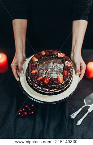 Woman Putting Cake Stand On Table
