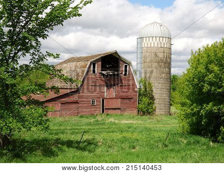 An abandoned barn and silo on a abandoned farmstead.