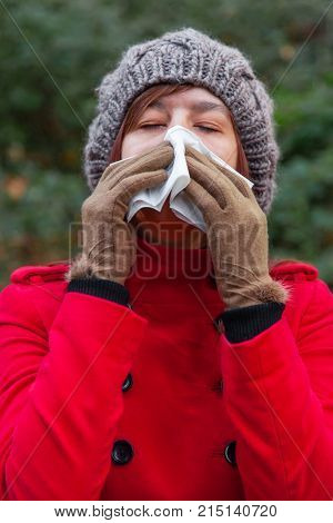 Young woman suffering from cold or flu blowing nose or sneezing on white paper handkerchief in forest wearing a red long coat or overcoat, a beanie and gloves during fall, autumn or winter