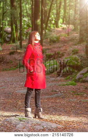 Woman enjoying the warmth of the winter sunlight alone on a forest park path wearing a red overcoat