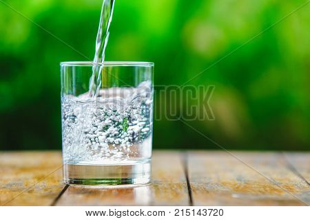 A glass of water on green background. The wooden table. Pure water with gas. Sparkling water