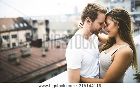 Romantic couple in love on rooftop hugging