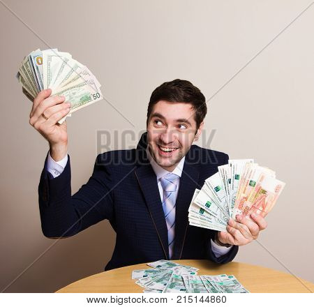 Young businessman sitting in a suit behind a desk with a fan of banknotes of dollars and rubles a mad look of joy. An amazing gain in the lives of ordinary people