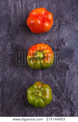 Appetizing, juicy, Bulgarian pepper, decomposed vertically orange and green, mature, and half-ripe, on a black background.