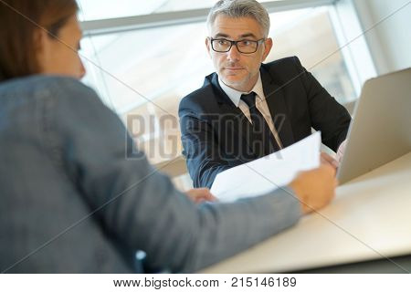 Woman in banker's office signing financial loan for project poster