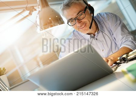 Office worker with headset on while having video conference