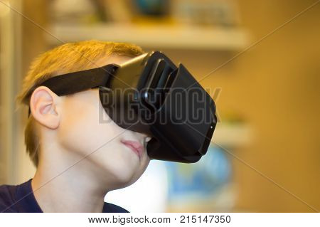 Happy teen boy wearing virtual reality goggles watching movies or playing video games. Cheerful smiling looking in VR glasses and making thumb up gesture. Child experiencing virtual reality.