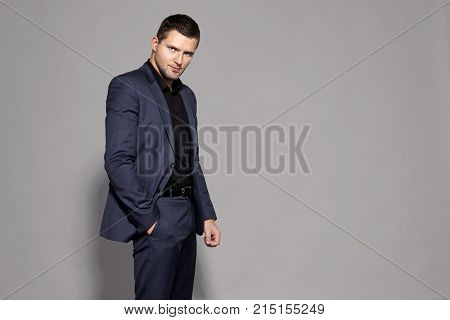 A middle-aged man is standing in an expensive suit on a gray background studio brutal courageous