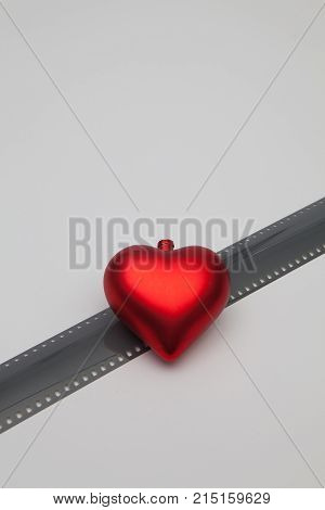 The red heart and the unrolled exposed 35mm film strips over a white background in a retro photography concept.