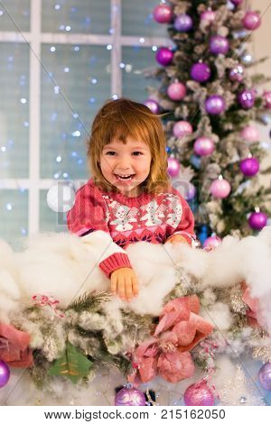 Happy baby girl playing with snowballs in the room. The girl throws a snowball