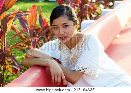 Mexican latin woman with ethnic dress sitting in garden park bench