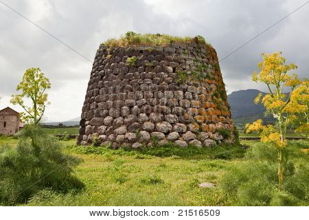 Nuraghe tower ruins and giant flower Sardinia Sardegna Italy archeological remnants of prehistoric building of bronze age ancient civilization tourism poster