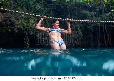 Girl playing with rope in Cenote sinkhole in  Riviera Maya at mayan Mexico