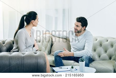 Pleasant therapy. Joyful positive delighted man sitting on the sofa and looking at his psychologist while being in a good mood