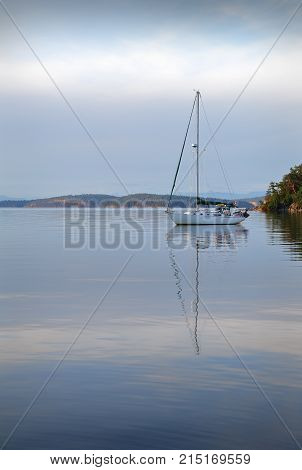 Gulf Islands Sailboat, British Columbia vertical. A calm anchorage in the Gulf Islands, British Columbia. Vertical.