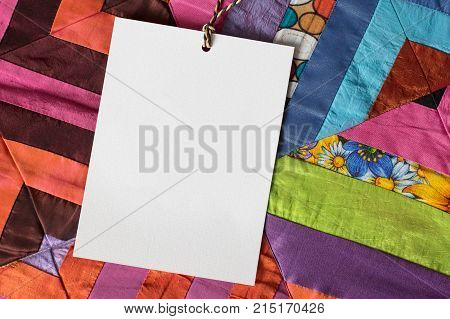 patchwork, greeting, handwork concept. close up of white very textured card on thin rope, it is placed on colorful quilt created of pieces in various coloures and patterns