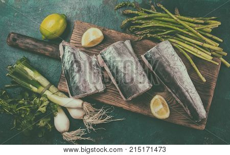 Food background with raw sawfish asparagus, lemon and herbs. Top view. Toned.