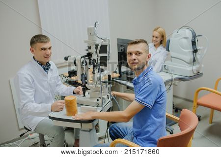 Young Beautiful Doctor/eye Specialist/optometrist In An Ophthalmologic Clinic Examines A Patient