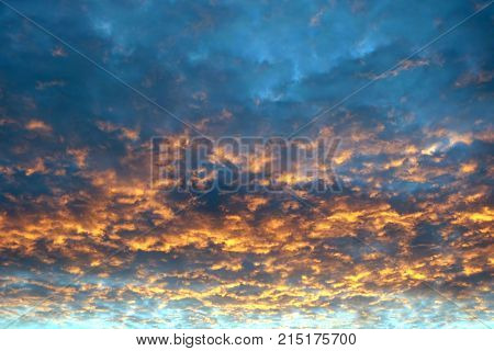 Beautiful colorful celestial sunset with many flamy clouds in sunset reflection in the evening poster