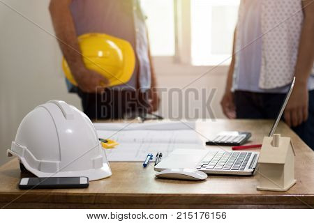 focus at safty helmet on working desk and two engineer standing and dicuss background