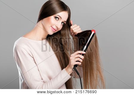 Beautiful smiling woman ironing long  hair with hair iron. Hairstyle.