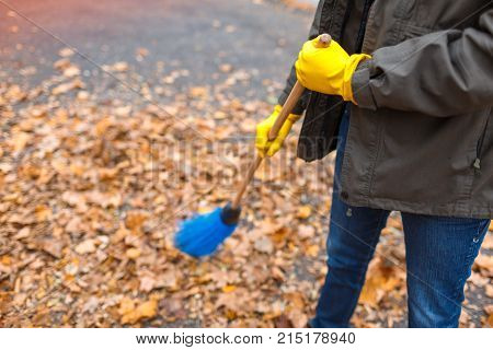 Hands of the father in yellow gloves sweeps a broom blue of the disgraced leaves in the autumn park