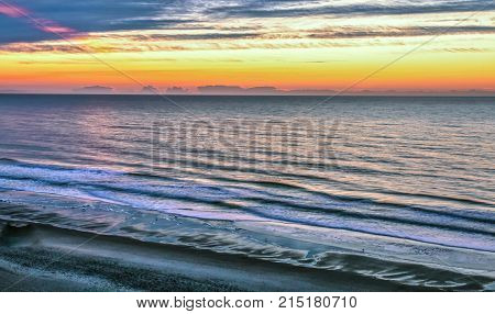 Ocean Coastal Sunrise Background. View of Atlantic coast with waves crashing on the shore and a sunrise at the horizon. Shot from above high angle view with copy space. Myrtle Beach, South Carolina.