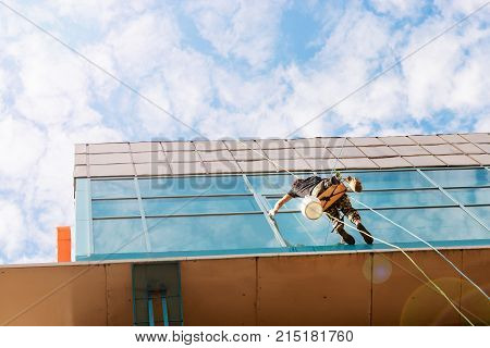 Industrial climber hanging on the clothesline and washes Windows glass facade modern building.