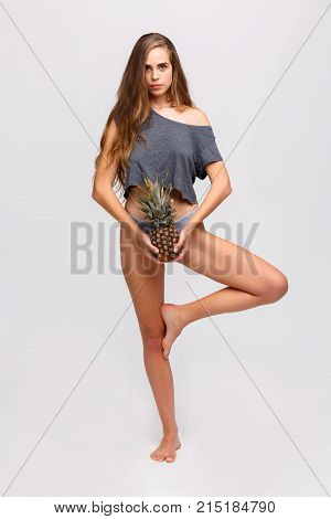 Young girl with a serious look holding a pineapple in hands standing at the level of cowards on one leg on a white background