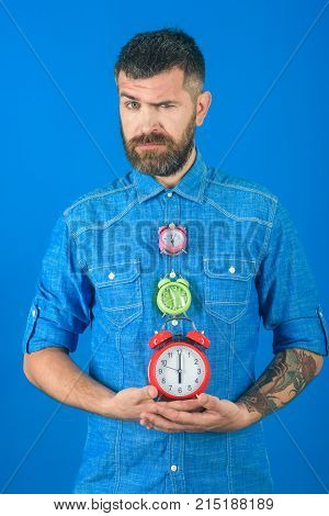 Man with beard hold alarm clock. Time and perfect morning. Time management and countdown. Overtime and urgency. Lifetime business and deadline watchmaker