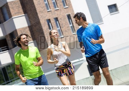 Two Young Men And Woman Running In Urban Enviroment