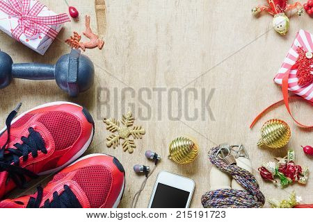 Fitness healthy and active lifestyles love concept dumbbells sport shoes skipping rope or jump rope and smart phone with Christmas decoration items on wood background. Working Out Merry Christmas concept.