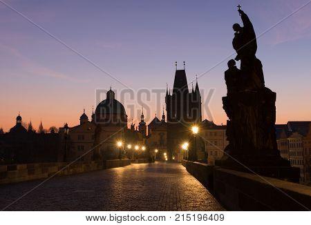 Charles bridge in twilight. Gas lamps illuminating cobblestones of Charles bridge in Prague Czech Republic. Silhouettes of towers