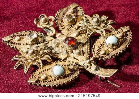 Silver brooch golden look in a form of leaf with white gemstones