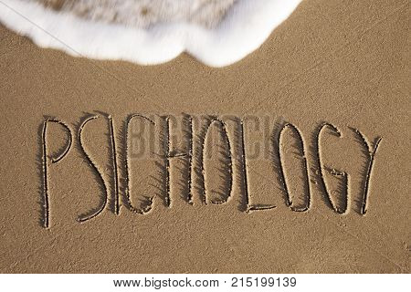 the psychology written in the sand of a beach, with sea foam on top
