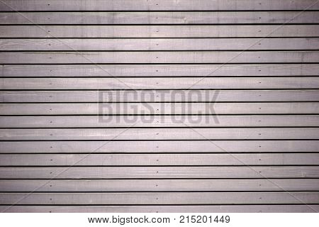 The close-up of the wooden paneling of a wall made of wooden panels.