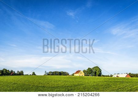 Yellow Farmhouse On A Rural Green Field